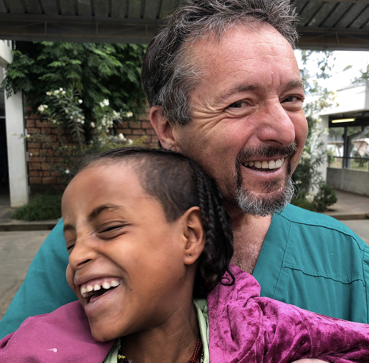 Dr. Tabin with an 8 year old girl who had been bilaterally blind for 3 years from cataract.  She had become aggressive and combative having retreated into a defensive world of blindness.  After surgery she became a laughing, joyous child.
